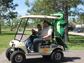 Two men in a golf cart with a person in an alligator costume on the back.
